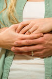 Close up of couple hands wearing wedding rings. With arms around Royalty Free Stock Photography