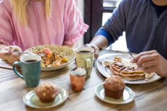 Couple eating breakfast at restaurant. Close up of couple having breakfast at restaurant, with focus on food and coffee cups royalty free stock photos