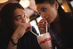 Close-up of couple having milkshake. In restaurant Stock Images