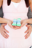 Close up of a couple holding baby shoes Stock Photo