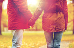 Close up of couple holding hands in autumn park. Love, relationships, season and people concept - close up of happy young couple holding hands in autumn park Stock Photos