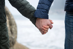 Close-up of couple holding hands on the beach Royalty Free Stock Photo
