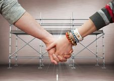 Close up of couple holding hands and flare against scaffolding in grey. Digital composite of Close up of couple holding hands and flare against scaffolding in Stock Image