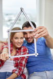 Close up of couple with house shape ruler Royalty Free Stock Images