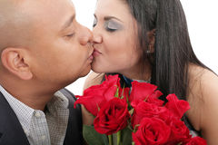 Close up of couple kissing holding a bouquet of red roses Stock Images