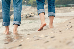 Close up couple legs image on the surf line Stock Photos