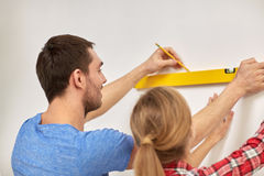 Close up of couple with level measuring wall Royalty Free Stock Image