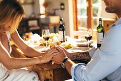 Couple having romantic meal at home. Close up of couple in love holding hands at home sitting at kitchen dining table. Close up of men and women having romantic Stock Photography