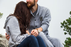 Close up, couple in love sitting on a mountain, hugging and look Stock Photo