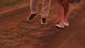 Close-up of couple in love walking along a country road in the summer at sunset.