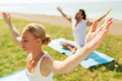 Close up of couple making yoga exercises outdoors Royalty Free Stock Photography
