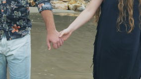 Close up couple man and woman hold hands and walk along the beach stock video footage
