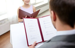 Close up of couple with menu at restaurant Royalty Free Stock Images