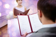 Close up of couple with menu at restaurant. Restaurant, food, eating and holiday concept - close up of couple with menu choosing dishes at restaurant over violet Royalty Free Stock Photos