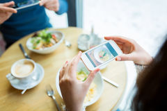 Close up of couple picturing food by smartphone Stock Photos