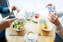 Close up of couple picturing food by smartphone. People, technology, eating and dating concept - close up of couple with smartphones picturing food at cafe or Stock Images