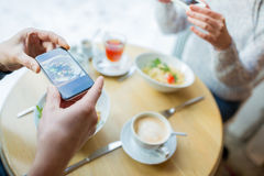 Close up of couple picturing food by smartphone. People, technology, eating and dating concept - close up of couple with smartphones picturing food at cafe or Stock Photo
