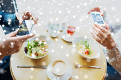 Close up of couple picturing food by smartphone. People, technology, eating and dating concept - close up of couple with smartphones picturing food at cafe or Stock Photos