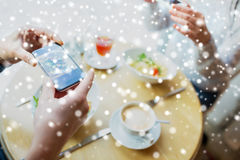 Close up of couple picturing food by smartphone. People, technology, eating and dating concept - close up of couple with smartphones picturing food at cafe or Royalty Free Stock Images