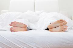 Close-up of couple's feet sleeping on bed Stock Images