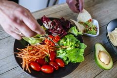 Close-up of couple`s hands eating avocado salad and plate of nac. Hos with homemade guacamole Royalty Free Stock Photography