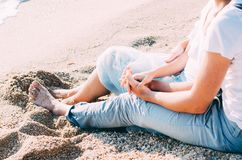 Close up of couple sitting sitting on the sand on the beach and holding hands. Summer love concept. Holiday relaxing, beach. Vacation. Couple enjoying their Royalty Free Stock Photos