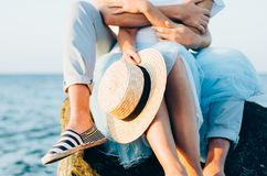 Close up of couple sitting on the stone near the sea or ocean. Photo of hands hugging and holding straw hat. Summer love concept. royalty free stock photography