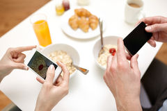 Close up of couple with smartphones at breakfast Stock Image