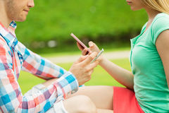 Close up of couple with smartphones outdoors. Summer, technology, virtual addiction and online communication concept - close up of couple texting with Stock Photo