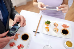 Close up of couple with smartphones at restaurant Stock Image
