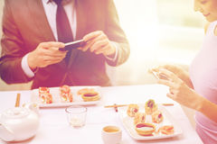 Close up of couple with smartphones at restaurant Royalty Free Stock Photos