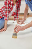 Close up of couple smearing wallpaper with glue Stock Photography