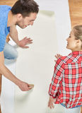 Close up of couple smearing wallpaper with glue Stock Image