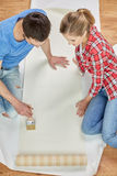 Close up of couple smearing wallpaper with glue Stock Photos