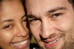 Close-up of a couple smiling in sunlight. Focus on male model Stock Image