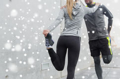Close up of couple stretching legs outdoors. Fitness, sport, training and healthy lifestyle concept - close up of couple stretching legs outdoors over snow Royalty Free Stock Photography