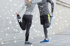 Close up of couple stretching legs outdoors. Fitness, sport, training and healthy lifestyle concept - close up of couple stretching legs outdoors over snow Stock Photography