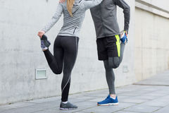 Close up of couple stretching legs outdoors Stock Images