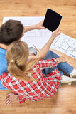 Close up of couple with tablet pc and blueprints Stock Image