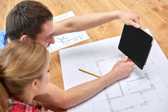 Close up of couple with tablet pc and blueprints Royalty Free Stock Photos