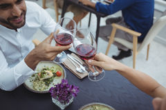 Close-up of couple toasting glasses of wine while having meal royalty free stock image