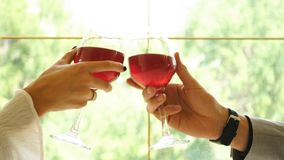 Close Up of Couple Toasting with red wine glass in restaurant. Mid adult Caucasian male and female hands toasting wine glasses stock video