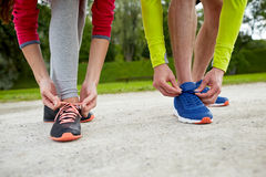 Close up of couple tying shoelaces outdoors. Fitness, sport, friendship and lifestyle concept - close up of couple tying shoelaces outdoors Royalty Free Stock Photos