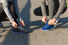 Close up of couple tying shoelaces outdoors. Fitness, sport, friendship and lifestyle concept - close up of couple tying shoelaces outdoors stock image