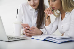 Close up of a couple of women at a table in office. One at her phone screen. Stock Image
