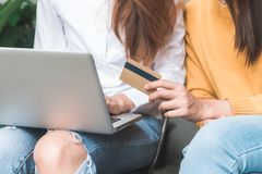 Close up of a couple young Asian women using her credit card while they do shopping online with her laptop. Young women shopping online in the garden holding Royalty Free Stock Photo