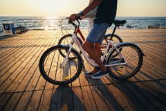 Close up of couple of young hipsters cycling together at the beach at sunrise sky at wooden deck summer time royalty free stock photography