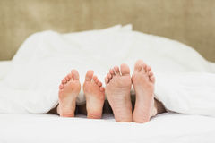 Close up of couples feet. In their bed Stock Photography