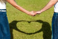 Close up of couples hands together with love sign. Royalty Free Stock Images