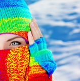 Close up on covered face with blue eyes. Close up portrait of a woman's covered face with beautiful blue eyes, female wearing colorful winter hat, girl having Stock Photos